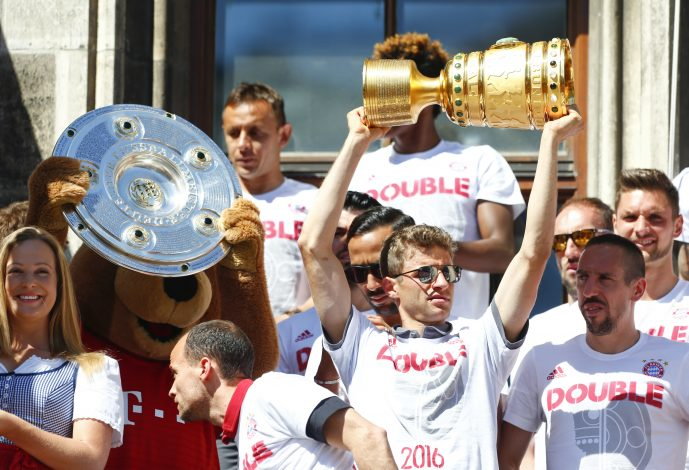 Football Soccer - Bayern Munich German Cup (DFB Pokal) victory parade - Munich, Germany - 22/05/16. Bayern Munich's Thomas Mueller and teammates celebrate with German soccer cup and German soccer championship, Bundesliga, trophies. REUTERS/Michaela Rehle - RTSFDSL