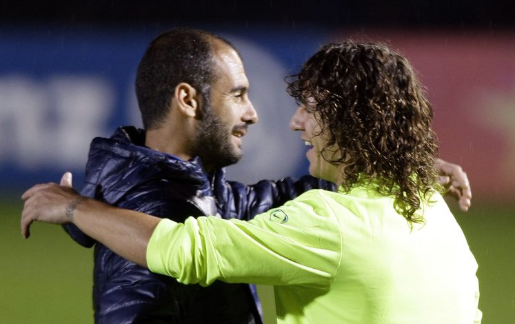 Barcelona's soccer player Carles Puyol (R) is embraced by his coach Pep Guardiola during a training session at Joan Gamper training Camp near Barcelona, December 29, 2009. REUTERS/Albert Gea (SPAIN - Tags: SPORT SOCCER) - RTR28F1Q