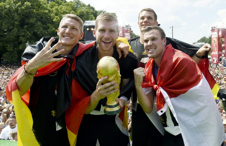 German national soccer players Bastian Schweinsteiger, Per Mertesacker and Manuel Neuer pose with the World Cup trophy during celebrations in Berlin, July 15, 2014. REUTERS/Markus Gilliar/Pool (GERMANY - Tags: SPORT SOCCER WORLD CUP) - RTR3Z05Y