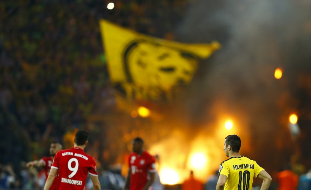 Football Soccer - Bayern Munich v Borussia Dortmund - German Cup (DFB Pokal) Final - Olympiastadion, Berlin, Germany - 21/05/16. Bayern Munich's Robert Lewandowski and Borussia Dortmund's Henrikh Mkhitaryan watch as supporters burn flares.       REUTERS/Michael Dalder     DFB RULES PROHIBIT USE IN MMS SERVICES VIA HANDHELD DEVICES UNTIL TWO HOURS AFTER A MATCH AND ANY USAGE ON INTERNET OR ONLINE MEDIA SIMULATING VIDEO FOOTAGE DURING THE MATCH.  - RTSFBBP