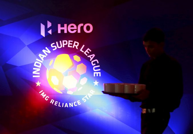 A waiter walks past a logo of Indian Super League before a news conference during the domestic player auction and draft in Mumbai, India, July 10, 2015. India's most prolific goal-scorer Sunil Chhetri drew the highest bid in Friday's auction and will join former France striker Nicholas Anelka at the Mumbai FC in the second edition of the Indian Super League (ISL). REUTERS/Danish Siddiqui - RTX1JUF2