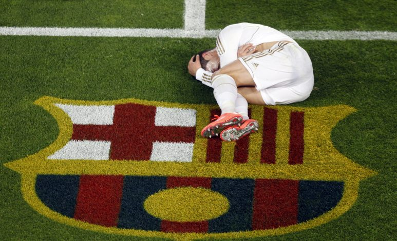 "Real Madrid's Cristiano Ronaldo grimances in pain after being tackled by Barcelona's Daniel Alves during their Spanish first division ""El Clasico"" soccer match at Nou Camp stadium in Barcelona April 21, 2012. REUTERS/Gustau Nacarino (SPAIN - Tags: SPORT SOCCER) - RTR311S5"