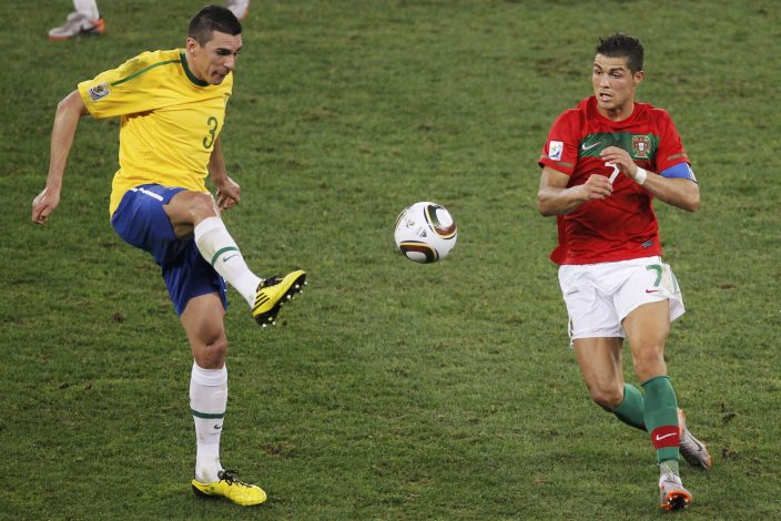 Brazil's Lucio (L) kicks the ball past Portugal's Cristiano Ronaldo during the 2010 World Cup group G soccer match at Moses Mabhida stadium in Durban June 25, 2010. REUTERS/Paul Hanna (SOUTH AFRICA - Tags: SPORT SOCCER WORLD CUP) - RTR2FPXY