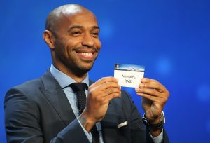 Thierry Henry holds a paper with the name of Arsenal.