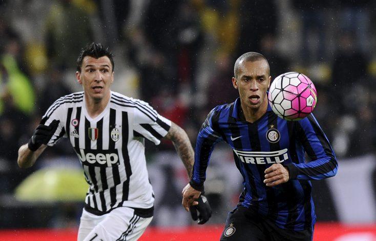 Juventus' Mario Mandzukic (L) in action against Inter Milan's Miranda (R).