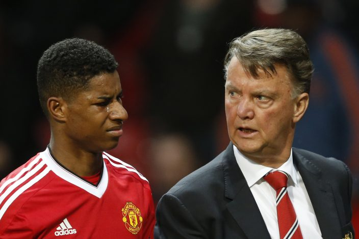 Marcus Rashford walks off at half time with Louis van Gaal.
