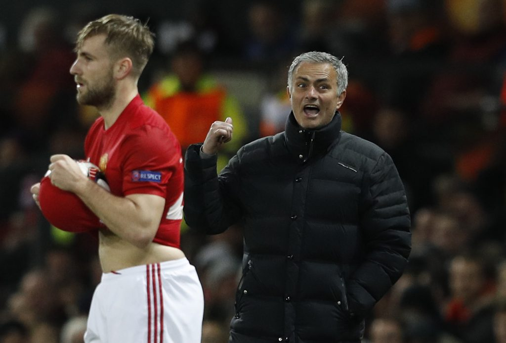 Luke Shaw prepares to take a throw as manager Jose Mourinho looks on.