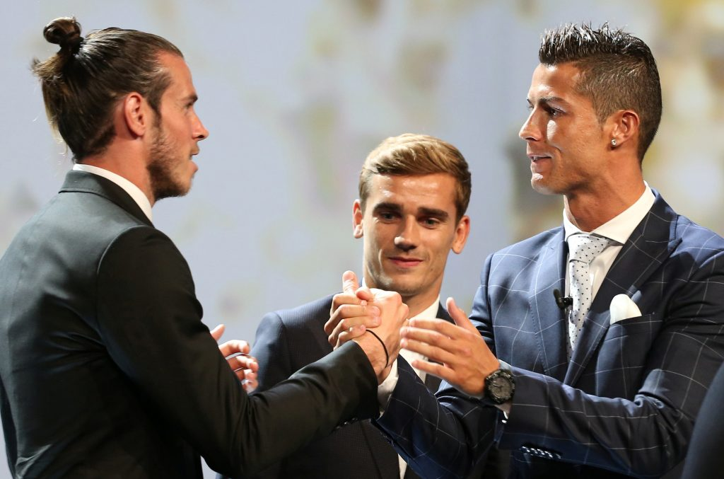 Real Madrid's Cristiano Ronaldo (R) reacts with Gareth Bale (L) and Antoine Griezmann (C) after he received the Best Player UEFA 2015/16 Award.