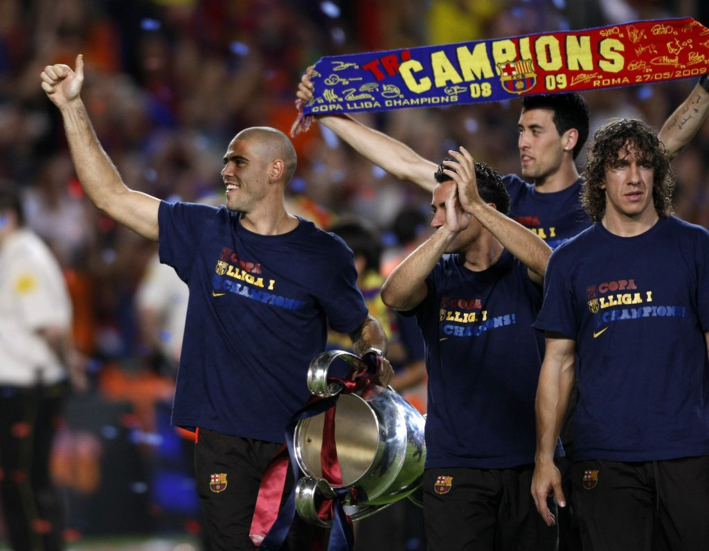 Victor Valdes (L-R) holds the Champions League trophy as he celebrates Barcelona's Champions League victory with teammates Xavi Hernandez, Sergi Busquets and Carles Puyol.