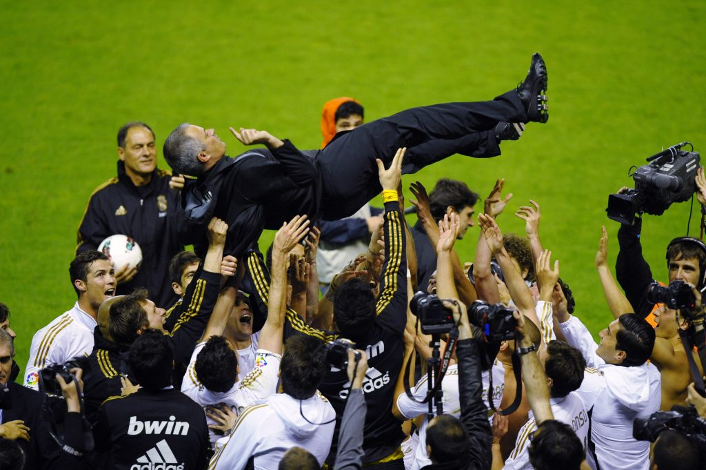 Real Madrid's coach Jose Mourinho is thrown in the air by his players.