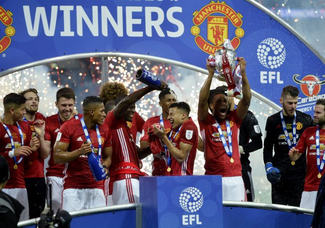 Manchester United's Eric Bailly pours champagne over Jesse Lingard as they celebrate with team mates and trophy after winning the EFL Cup Final.
