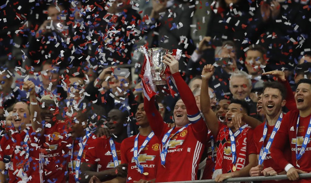 Manchester United's Wayne Rooney celebrates by lifting the trophy at the end of the match.