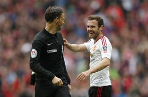 Manchester United's Juan Mata with referee Mark Clattenburg.