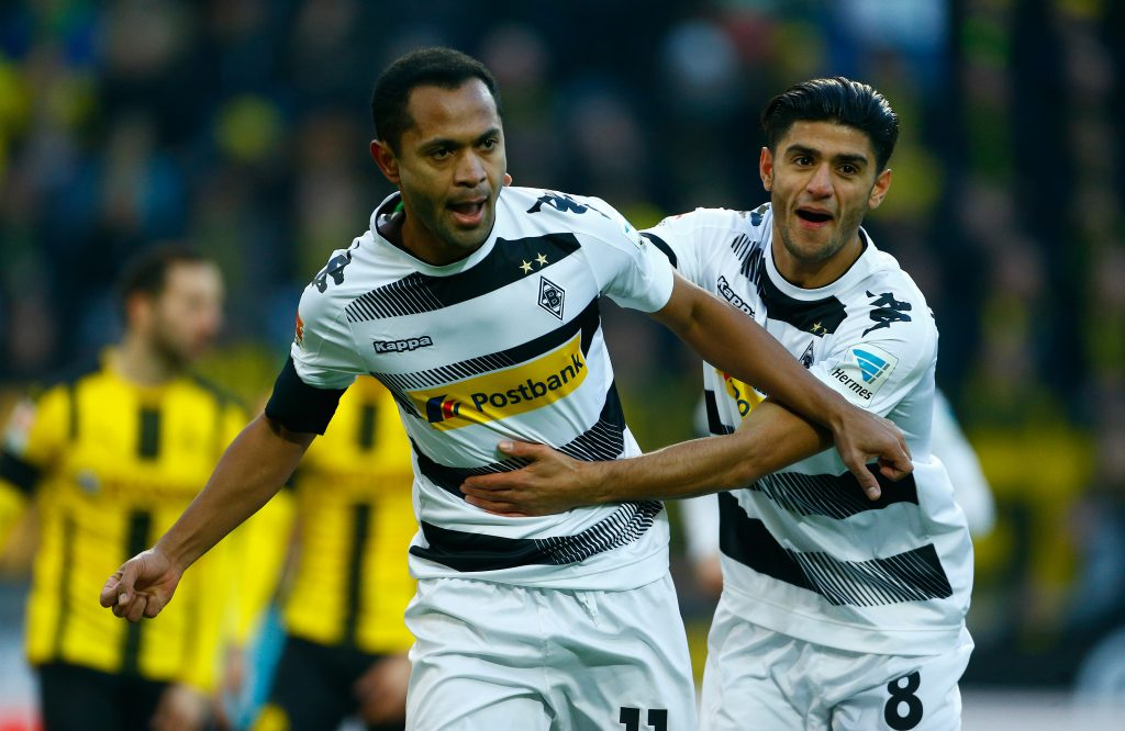 Borussia Moenchengladbach's Raffael celebrates with his teammate Mahmoud Dahoud after scoring a goal.
