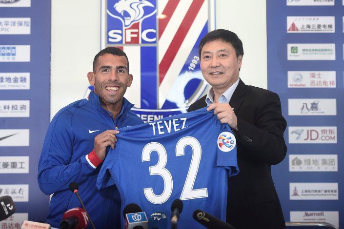 Carlos Tevez holds a team shirt with Wu Xiaohui, Chairman of Shanghai Greenland Shenhua Football Club.