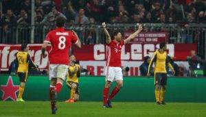 Bayern Munich's Xabi Alonso celebrates after Robert Lewandowski scores their second goal.