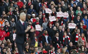 Arsenal manager Arsene Wenger as fans protest with signs.