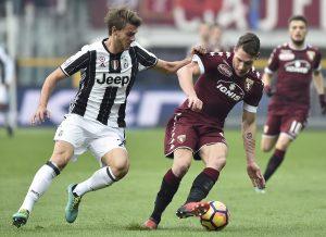 Juventus' Daniele Rugani in action with Torino's Andrea Belotti.