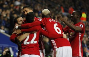 Manchester United's Juan Mata celebrates with teammates after scoring their third goal.