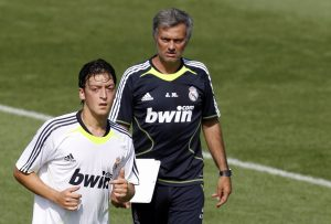 Mesut Ozil of Germany (L) runs past coach Jose Mourinho during their training session.