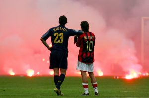 Inter Milan's Materazzi and Rui Costa of AC Milan wait on the pitch.