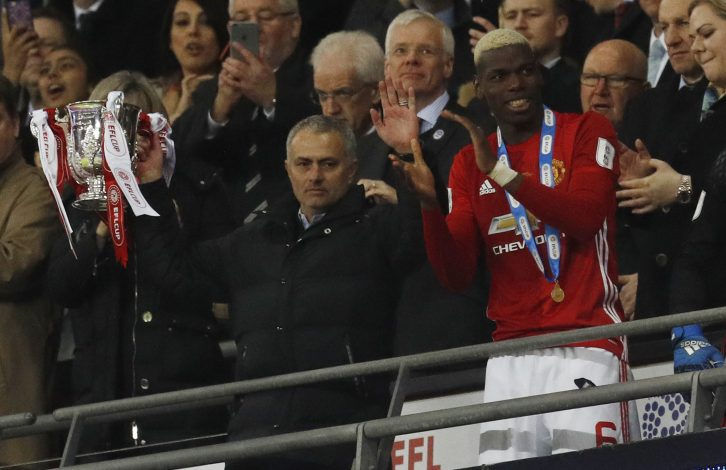 Manchester United manager Jose Mourinho lifts the trophy to celebrate winning.