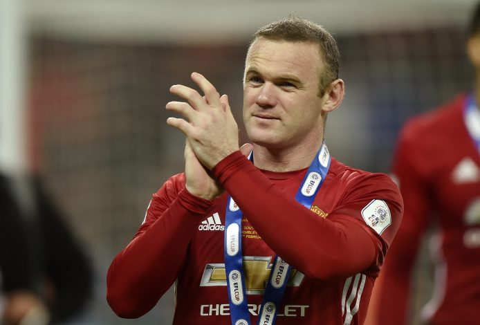 Manchester United's Wayne Rooney applauds fans as he celebrates winning the EFL Cup.