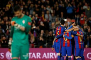 Barcelona's players celebrate a goal against Sporting Gijon's Cuellar.