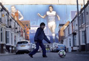 Fan plays with a ball outside the stadium before the game.