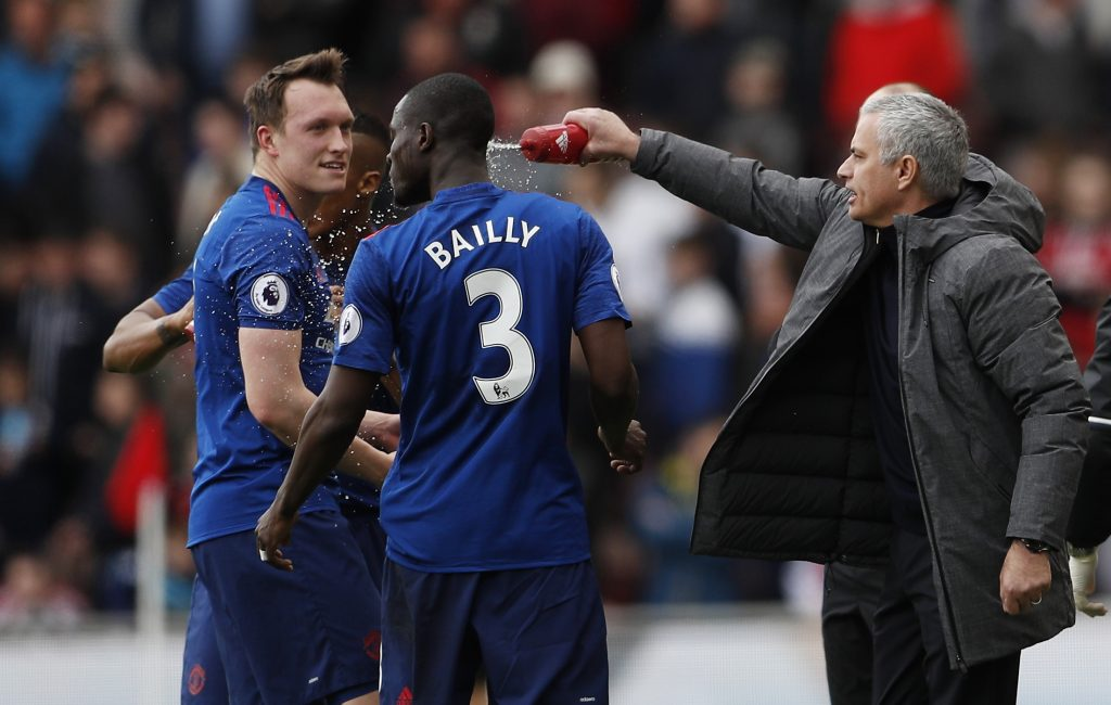 Eric Bailly is squirted with water by manager Jose Mourinho as Phil Jones looks on.