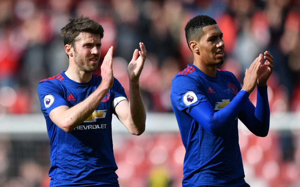 Manchester United's Michael Carrick and Chris Smalling applaud fans after the game.