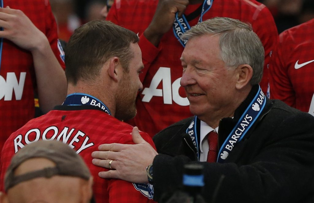 Manchester United manager Alex Ferguson speaks with Wayne Rooney (L).