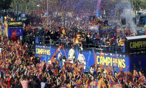 Barcelona's players celebrate on a bus with their supporters during their victory parade.