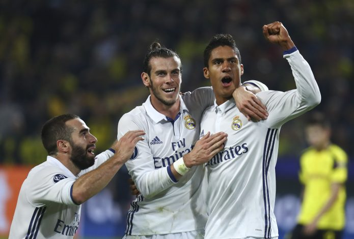 Real Madrid's Raphael Varane reacts with Gareth Bale and Dani Carvajal.