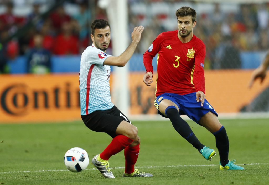 Spain's Gerard Pique in action with Turkey's Oguzhan Ozyakup.