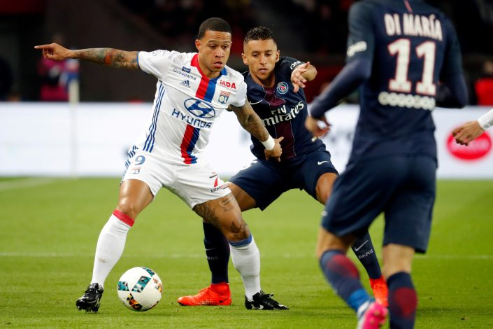 Marquinhos of Paris Saint Germain in action against Memphis Depay of Olympic Lyon.