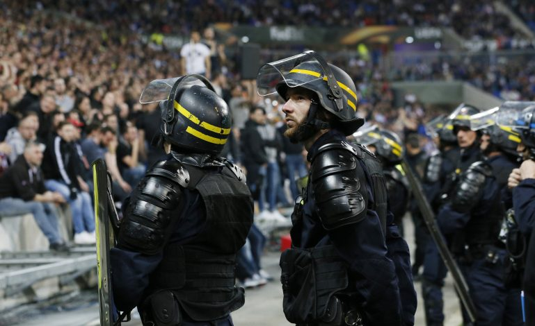 Police officers by the pitch after Lyon and Besiktas fans clashed in the stands.