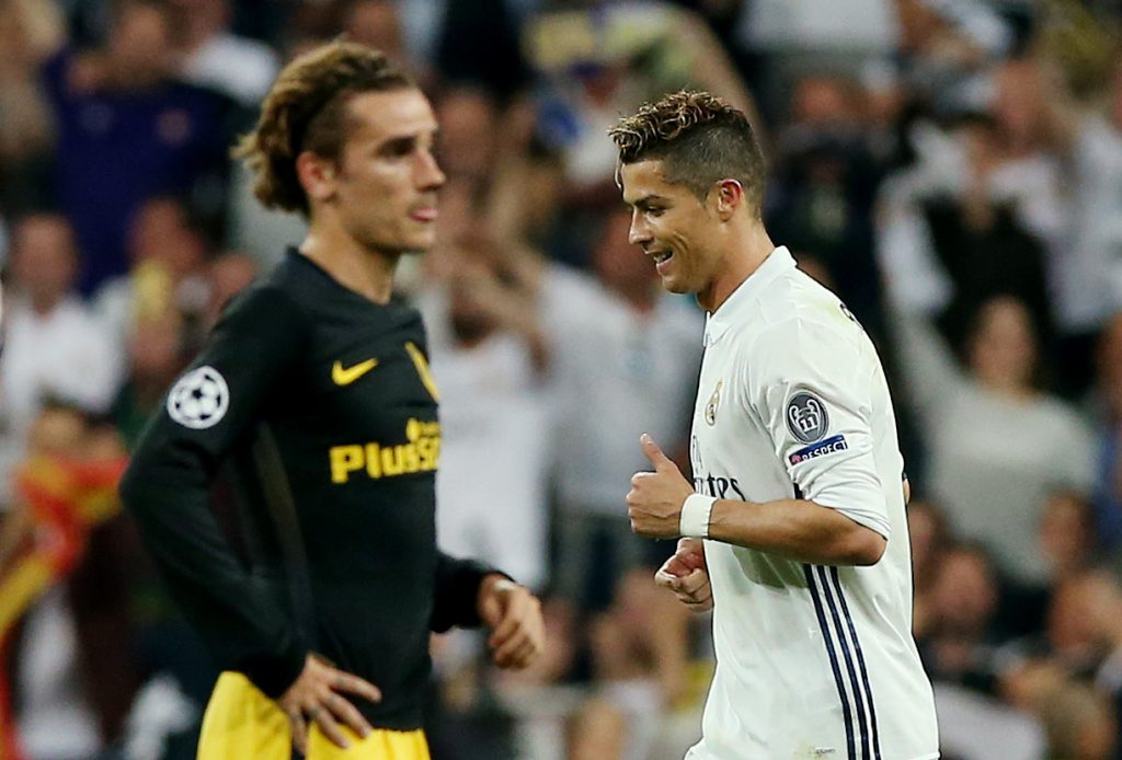 Atletico Madrid's Antoine Griezmann looks dejected as Real Madrid's Cristiano Ronaldo celebrates scoring their third goal and completing his hat trick.