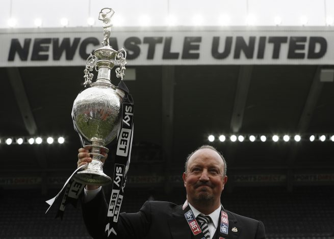 Newcastle manager Rafael Benitez celebrates winning the league with the trophy.