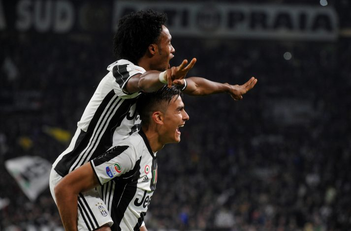 Juventus' Paulo Dybala (bottom) celebrates with his team mate Juan Cuadrado after scoring his second goal.
