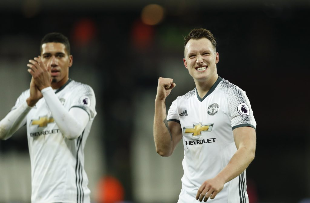 Manchester United's Phil Jones and Chris Smalling (L) celebrate after the game.