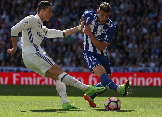 Real Madrid's Cristiano Ronaldo (L) and Alaves' Theo Hernandez in action.