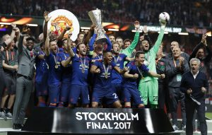 Manchester United celebrate winning the Europa League with the trophy.