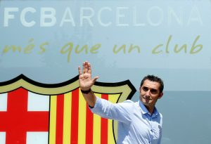 Coach Ernesto Valverde poses in front of FC Barcelona's giant logo.