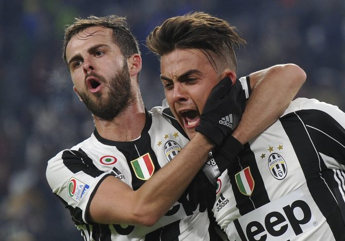 Juventus' Paulo Dybala celebrates with teammate Miralem Pjanic after scoring a penalty against Bologna.