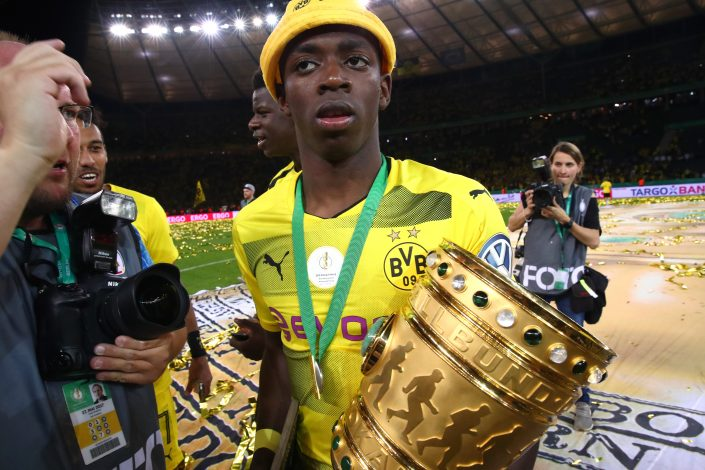 Borussia Dortmund's Ousmane Dembele celebrates with the trophy.