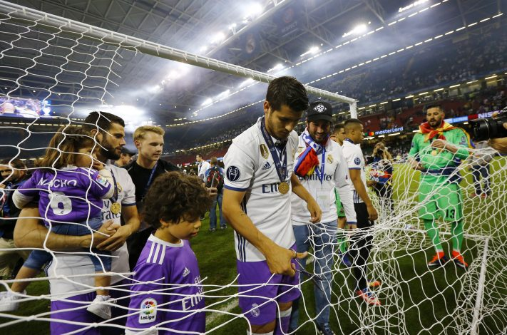 Real Madrid's Alvaro Morata cuts a part of the netting from the goal after winning the UEFA Champions League Final.