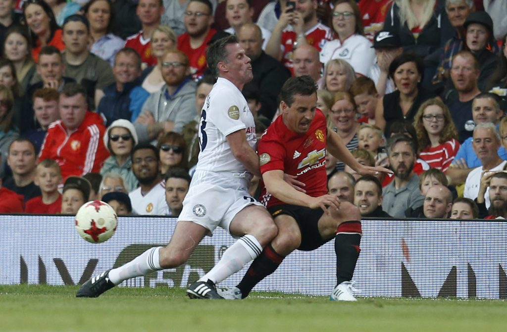 Michael Carrick All-Stars' Jamie Carragher in action with Manchester United '08 XI's Gary Neville.