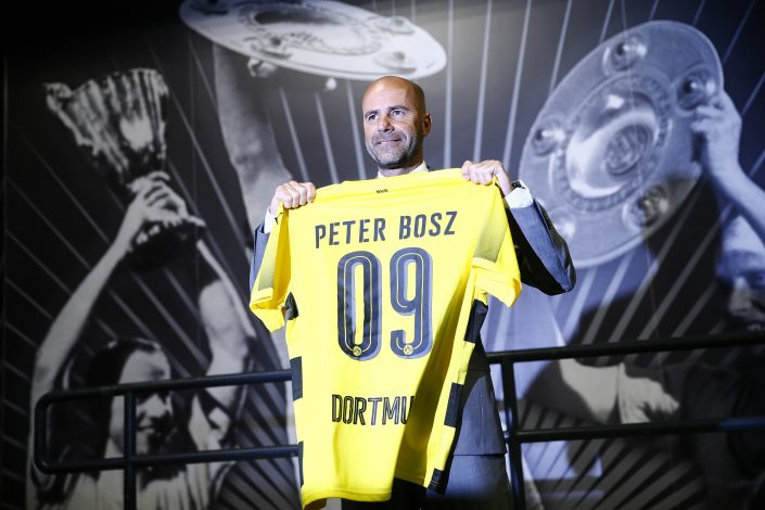 Dutch soccer coach Peter Bosz poses with a jersey as he is presented to the media as new coach of German soccer cup winner Borussia Dortmund.