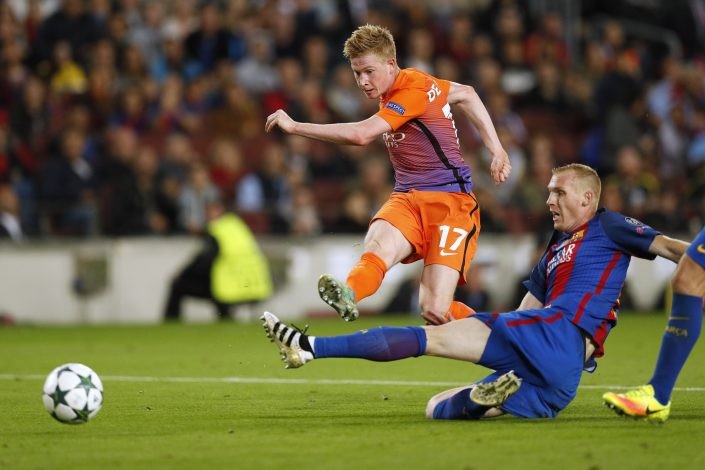 Manchester City's Kevin De Bruyne shoots at goal under pressure from Barcelona's Jeremy Mathieu.